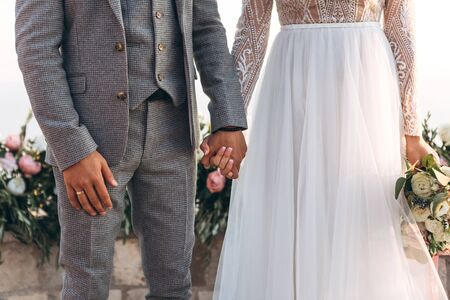 The bride and groom hold hands during the wedding ceremony. Stock Photo