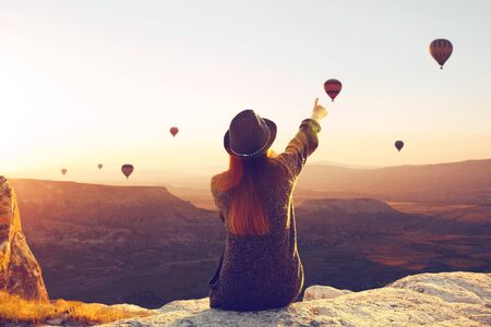 A woman in solitude sits on top of a mountain and admires the flight of hot air balloons in Cappadocia in Turkey. Digital detox and soul search Stock fotó