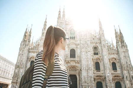A tourist or student with a backpack looks at the sights in Milan in Italy. She admires the Duomo Cathedral in the town square.