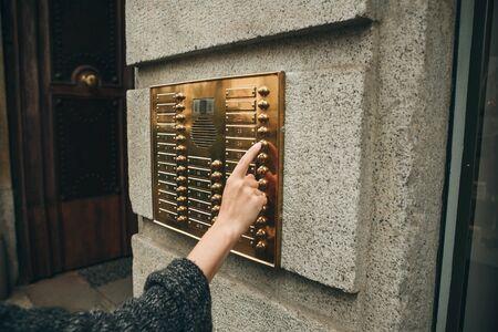 Female hand presses the intercom button to access inside.