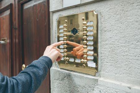 Una mano maschile preme un pulsante del citofono per accedere all'interno. Archivio Fotografico