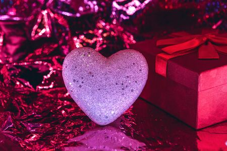 Heart and box with a gift on a trendy glowing red background. Valentine's day celebration or wedding concept or other love event. Reklamní fotografie