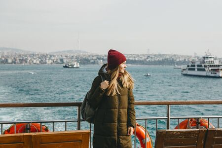 A student or tourist girl is standing on the deck or sailing on a ferry along the Bosphorus in Istanbul and enjoys beautiful views.