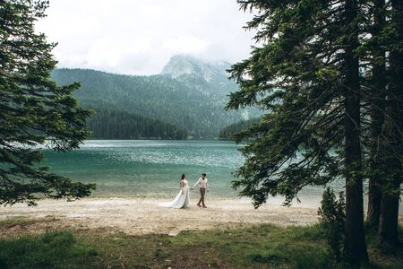 Young beautiful couple of newlyweds hold hands and walk by the lake during their honeymoon or they just got married