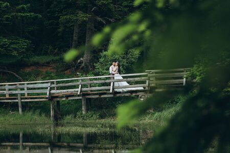 Groom with a bride or a man with a woman on a bridge in a forest near a lake. Wedding in nature or solitude for two.