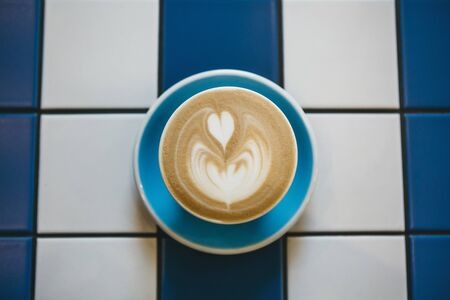 Closeup of fresh aromatic cappuccino coffee in a blue mug on a table of blue and white ceramic tiles. 스톡 콘텐츠