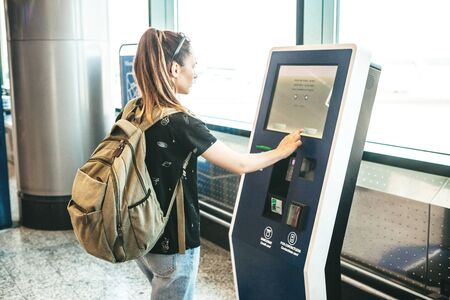 Girl tourist or student buys a ticket for transport in the self-service terminal