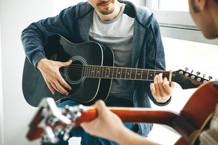 Learning to play the guitar. The teacher explains to the student the basics of playing the guitar. Individual home schooling or extracurricular lessons.