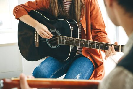 Learning to play the guitar. The teacher explains to the student the basics of playing the guitar. Individual home schooling or extracurricular lessons. Standard-Bild