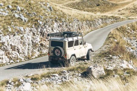 SUV rides on a road in the mountains. Extreme sport or road trip or adventure.