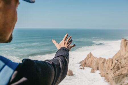 Tourist shows his hand into the distance at the ocean or sea