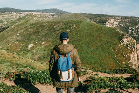 Hiker with backpack on a background of natural hilly landscape.