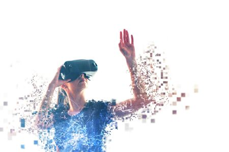 A girl in virtual reality glasses is pixelated or scattered into pixels. VR concept. Modern technologies.