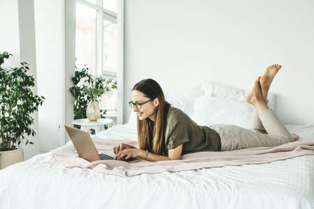 Positive girl student lies in bed and uses a laptop. She is texting or surfing online on the Internet.
