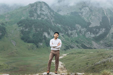 Portrait of a handsome young Kazakh man on a background of mountains. 版權商用圖片