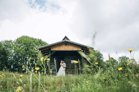 The bride and groom are standing next to the house. Rural or rustic scene 版權商用圖片