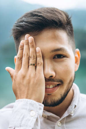 Young adult handsome positive groom closes his eyes with his hand and shows a wedding ring on his hand. 版權商用圖片