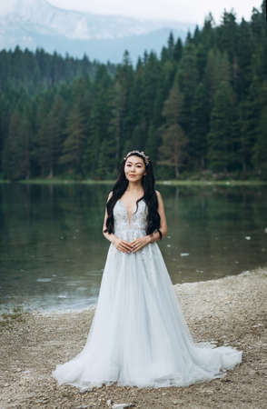 Portrait of a beautiful elegant bride in a white traditional dress on a lake background