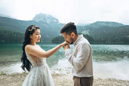 Kazakh groom gently kisses the hands of his bride