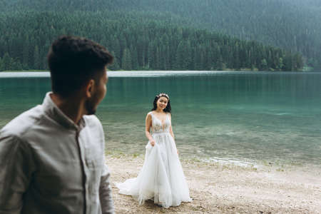Beautiful young Kazakh bride in a white dress is walking on the background of the lake. The groom is looking at her. 版權商用圖片