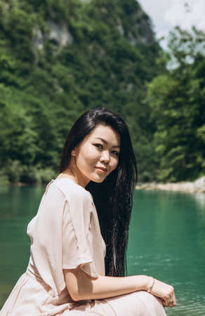 Portrait of a young adult beautiful Kazakh girl on the river bank on a background of nature.