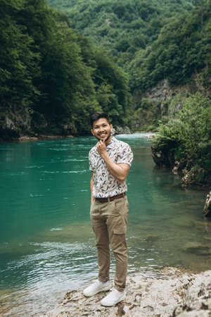 Portrait of a handsome positive young Kazakh man on a background of nature.