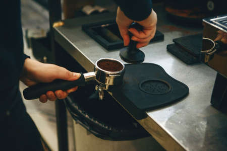 Barista presses ground coffee using tamper. Close-up view on hands with portafilter 版權商用圖片