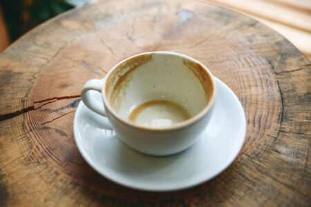 Empty cup after drunk coffee on a wooden table. Concept for ending a meeting or something else.