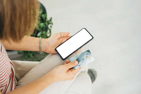 Online shopping. Girl with a cell phone with white blank screen for mockup and a credit card or a bank card in hands.