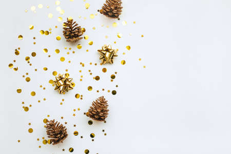 Festive golden bows and cones on a white background with confetti. Christmas or New Year background. Nearby copy space or space for text. Standard-Bild