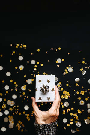 The person holds in his hand a box with a gift on a black background with confetti. Festive New Year and Christmas or other holiday background. Reklamní fotografie