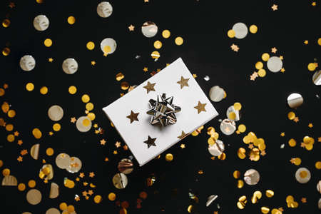 Box with a gift and a lot of confetti on a black background. Festive Christmas or New Year or other holiday concept background.