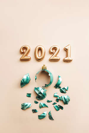 Gold numbers 2021 next to a broken Christmas tree toy on a pink background.