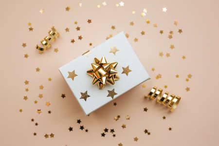 Gift box on a pink background with golden confetti. Festive background.