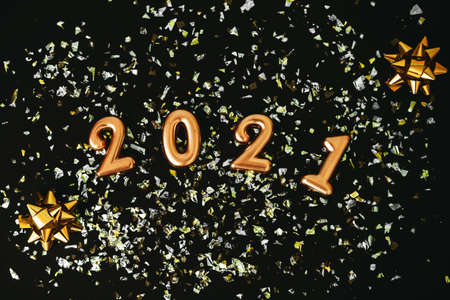 Gold numbers 2021 and glowing sparkles on a dark or black background. Christmas or New Year background. Reklamní fotografie