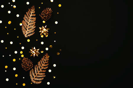 Gold bows, pine cones and confetti. Christmas or New Year dark background. There is empty space for text nearby. Reklamní fotografie