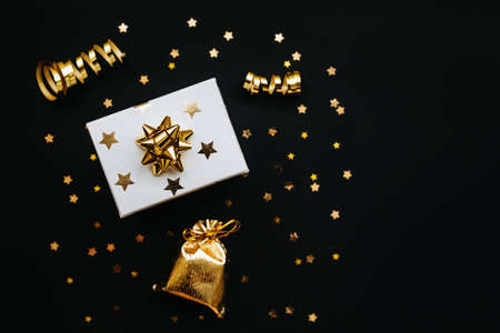 Gift box and various golden items on a black or dark background. Festive conceptual Christmas or New Year background or Black Friday sale Reklamní fotografie
