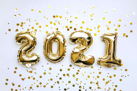 Golden inflatable holiday numbers 2021 on white background with golden confetti Christmas or New Year concept background.