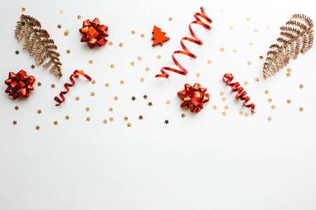 Gold and red Christmas items on a white background. Christmas or New Year conceptual background. There is empty space for text at the bottom.