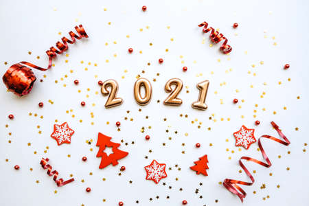 Gold numbers 2021 on a white background with confetti and various red holiday items. Christmas or New Year conceptual background.