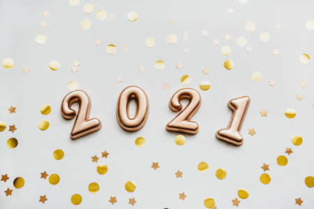 Gold holiday numbers 2021 on a white background with gold confetti. Christmas or New Year conceptual background. Reklamní fotografie