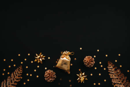 Various festive items and decorations in gold color on a dark or black background. Top space for text or copy space. Christmas or New Years concept. Reklamní fotografie