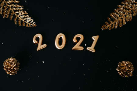 Gold numbers 2021 and golden trinkets on dark or black backgrounds. Christmas or New Year background.