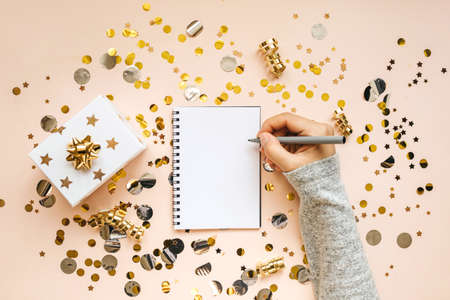 The girl writes goals for the New Year or a wish list or a letter to Santa in a notebook. Reklamní fotografie
