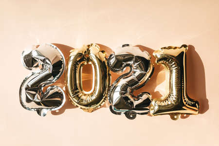 Gold and silver numbers 2021 on a pink background. New Year and Christmas celebration concept in minimal style.