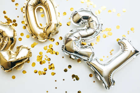 Gold and silver numbers 2021 and festive confetti on a white background. Conceptual New Year and Christmas background.