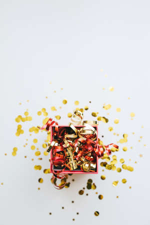 Open festive box with tinsel and confetti. Celebrating Christmas or New Years or winning a prize or a promotion or other holiday concept.