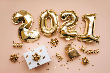 Top view of golden 2021 numbers and gifts and holiday decorations on pink background. New Year and Christmas background.