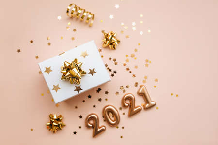 Top view of gift box and golden confetti and numbers 2021 on pink background. Festive New Year and Christmas background. Reklamní fotografie
