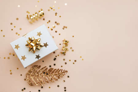Gift box and various golden items on a pink background. Festive conceptual Christmas or New Year background. Nearby copy space.